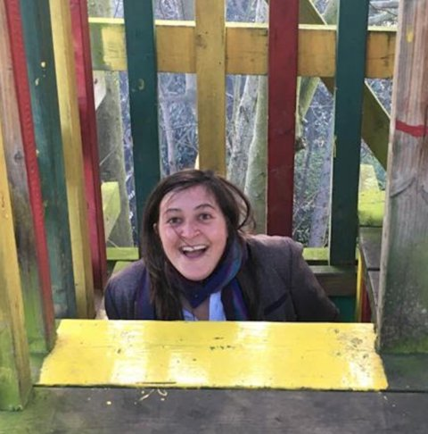 Photo of Hannah Cowan, in a children's playground, head and torso emerging as she climbs up a ladder onto a platform