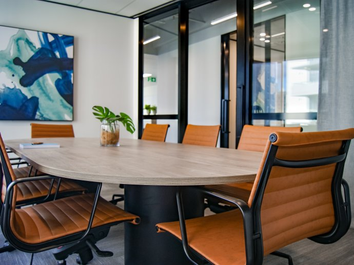 Photo of a meeting room, a blue painting is on the far wall and a large oval table is surrounded by black and orange chairs; a green plant in a pot sits on the table