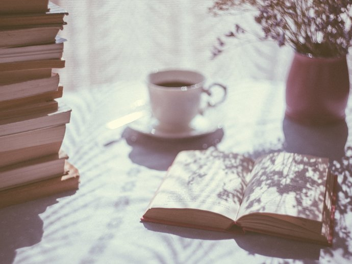Photo of a stack of books, with one book laying open next to it, with a cup of tea and some flowers in the background.