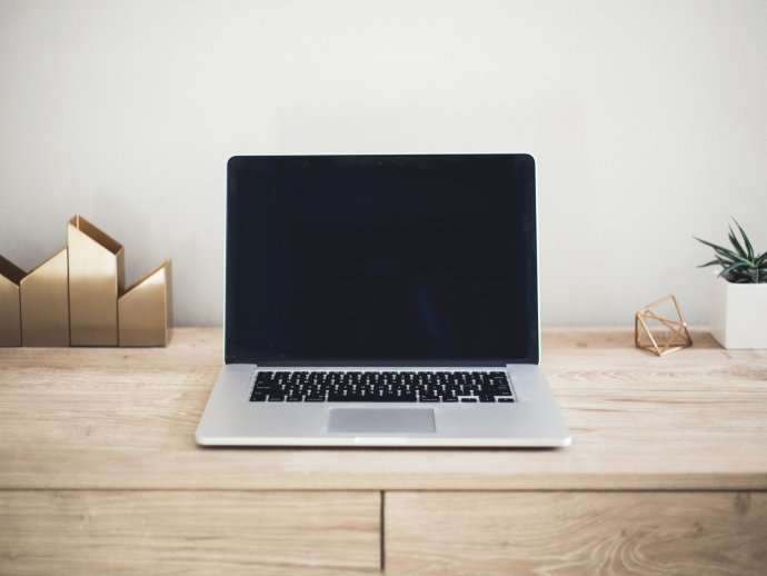 Picture of an open laptop computer on a wooden desk