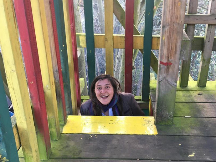 Photo of Dr Hannah Cowan emerging from a childen's climbing frame in a playpark