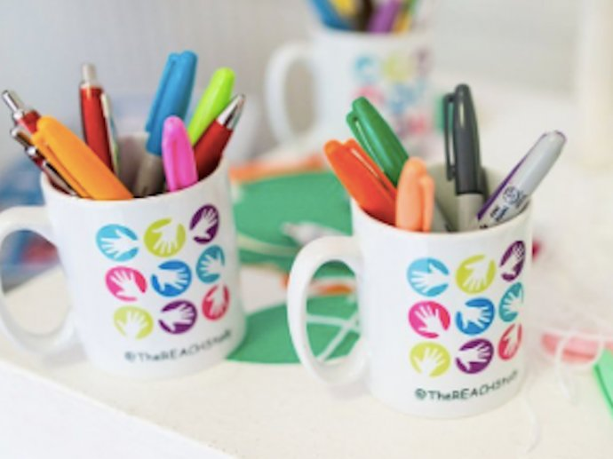 Photo of two mugs with the REACH study logo on them, and assorted pens inside