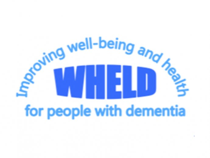 """WHELD logo - the word wheld with """"improving wellbeing and health for people with dementia"""" written around it."""