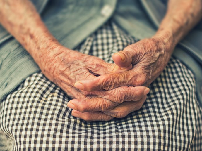 An older person sitting with their hands in their lap - the picture shows only the hands and lap.