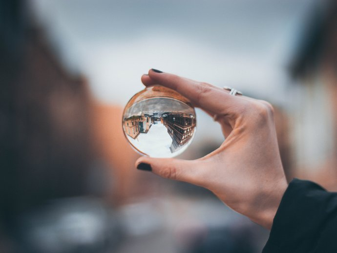 Picture of a hand holding a glass ball, which brings the blurred background into focus