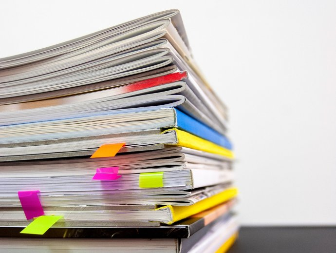 Photo of a stack of magazines, with post-it note bookmarks in several of them