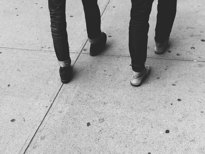 Two pairs of legs of people walking, the picture is cut off at the top so all you can see is legs and shoes on a concrete pavement.