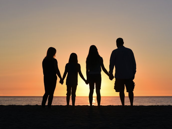 Photo of four people holding hands, silhouetted against the sunset on a beach
