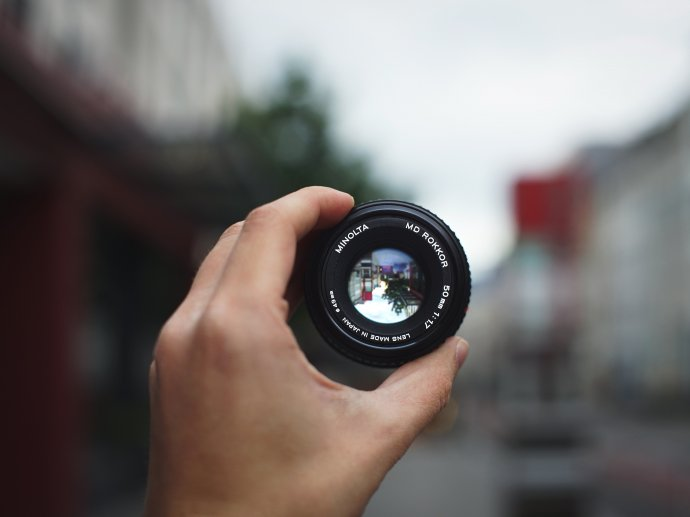Picture of a hand holding up a camera lens over a blurred background, but through the lens everything is in focus