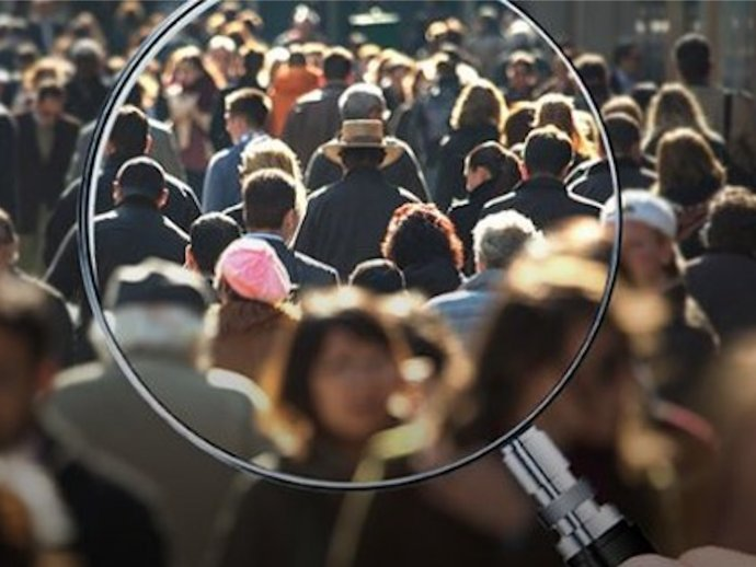 Magnifying glass bringing a picture of a crowd of people into focus