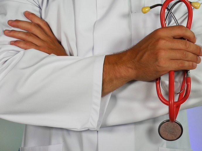 A doctor in a white lab coat holding a red stethoscope