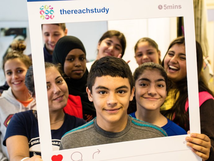 """Picture of children holding a cutout frame of an Instagram post saying """"REACH Study"""""""