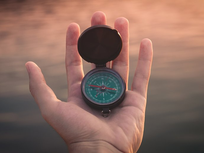 Picture of an open hand with a compass in the palm