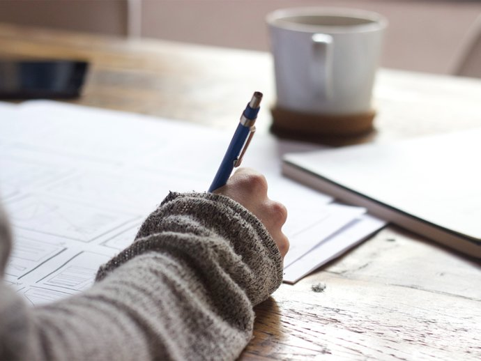 Picture of someone writing with a pen and paper