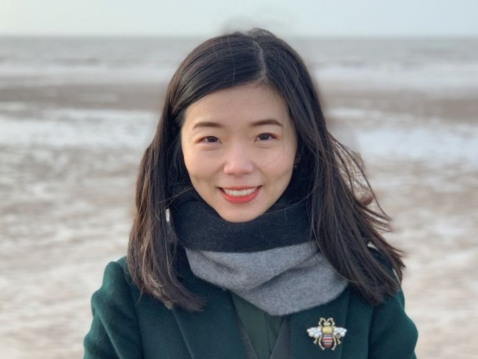 Jia Liu, in a jacket and scarf with a beach in the background
