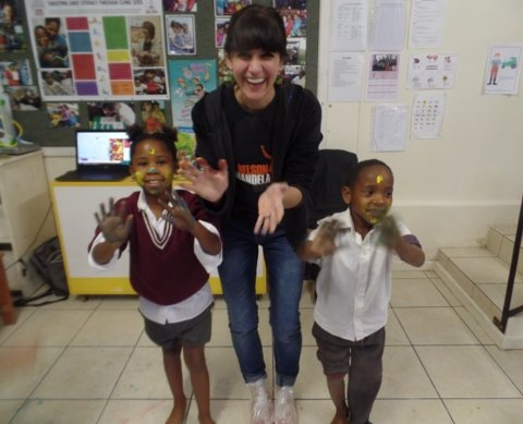 Photo of Sharli with two children as part of her early career work in South Africa
