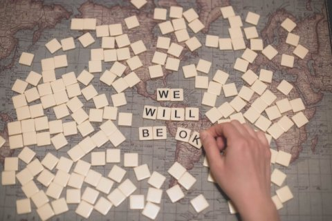 "Picture of scrabble tiles spelling out ""we will be ok"" over a map of the world"